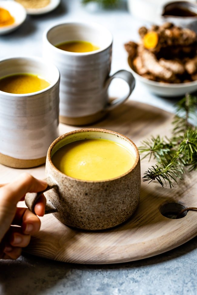A cup of turmeric golden milk a woman is holding it