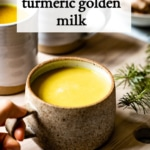 turmeric golden milk placed on a board by a person
