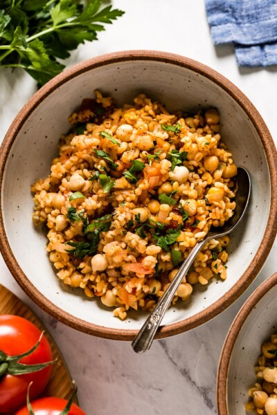 Bulgur pilaf in a bowl with a spoon on the side from top view