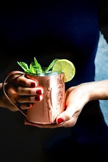 Kentucky Mule recipe in the hands of a woman.