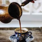 A cup of freshly brewed Turkish coffee photographed from the front view