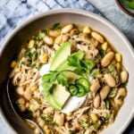Healthy white chicken chili in a bowl and garnished with chili toppings like avocados and cilantro