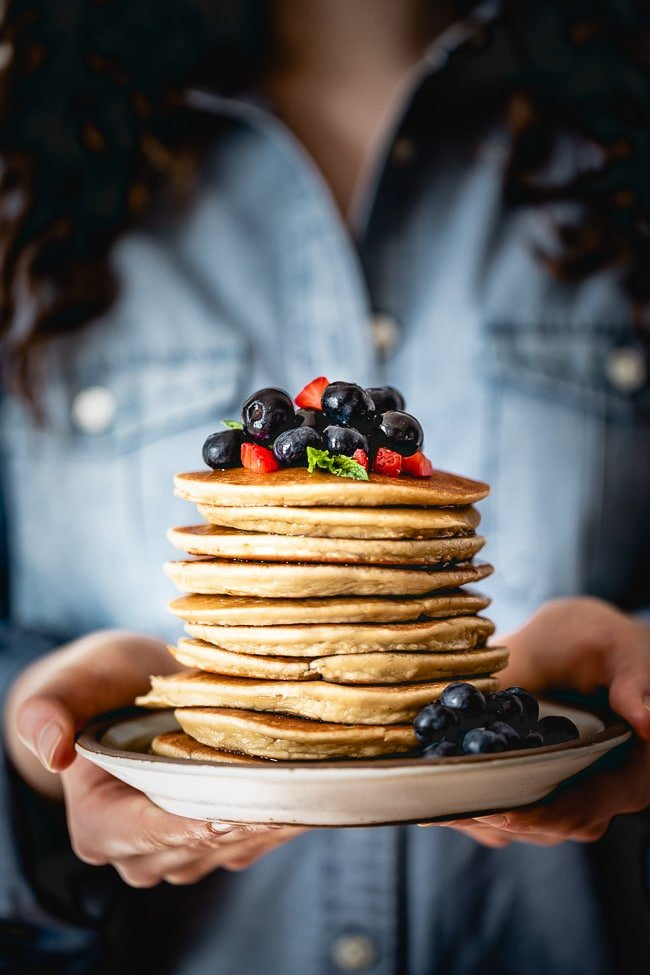 Easy Almond Flour Pancakes topped off with fresh fruit in a woman's hand