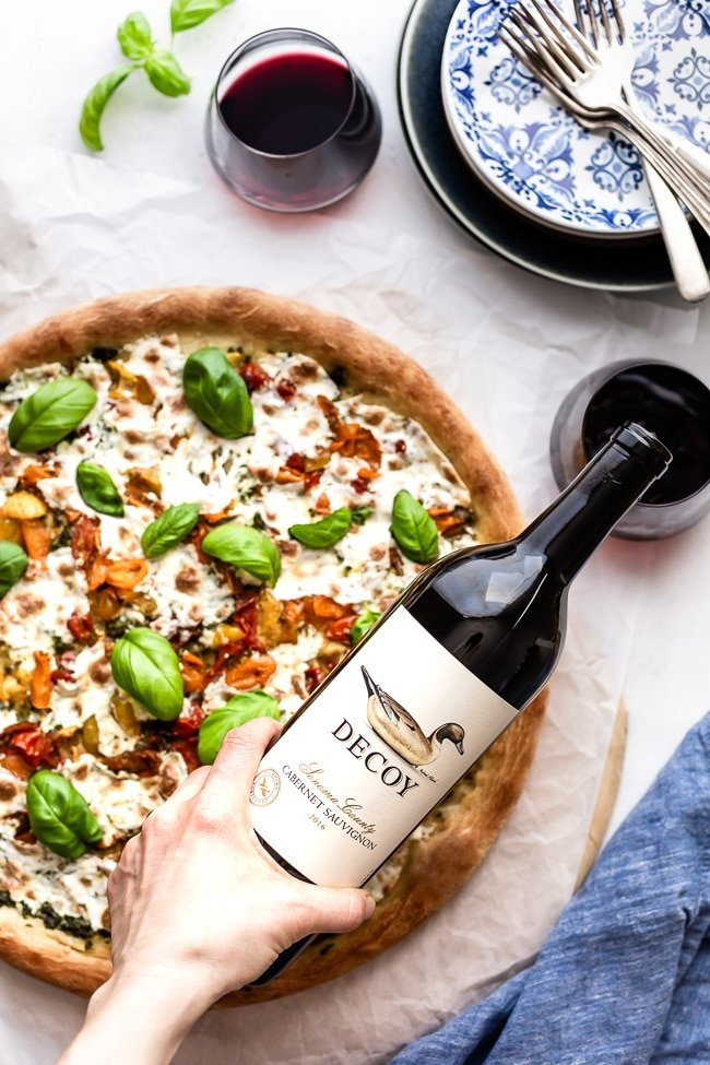 This delicious Homemade Caprese Pizza is filled with mozzarella, tomato, and basil is being served with a bottle of wine.