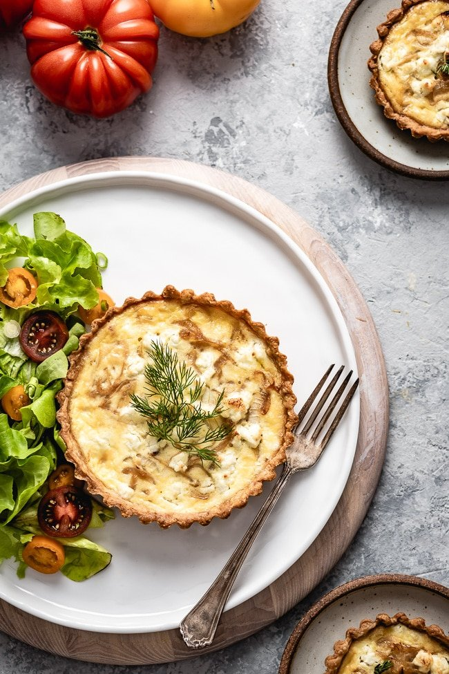 A single serving of Caramelized onion and goats cheese quiche is served with a salad and photographed from the top view.