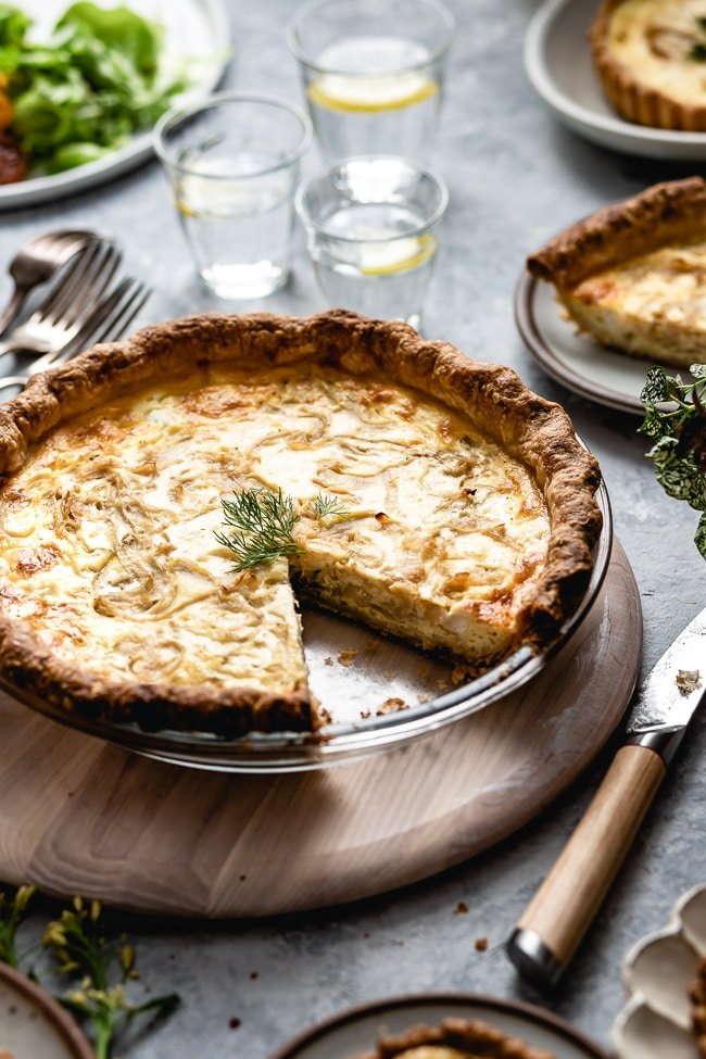 A large (9-inch) Goat cheese and caramelized onion quiche is photographed from the front.