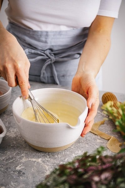 a woman is photographed from the front view as she is mixing the filling.