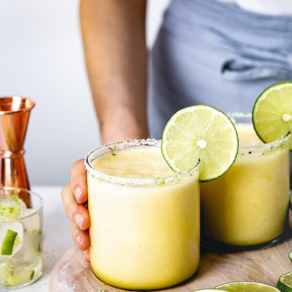 a woman is serving Pineapple Margaritas garnished with a lime