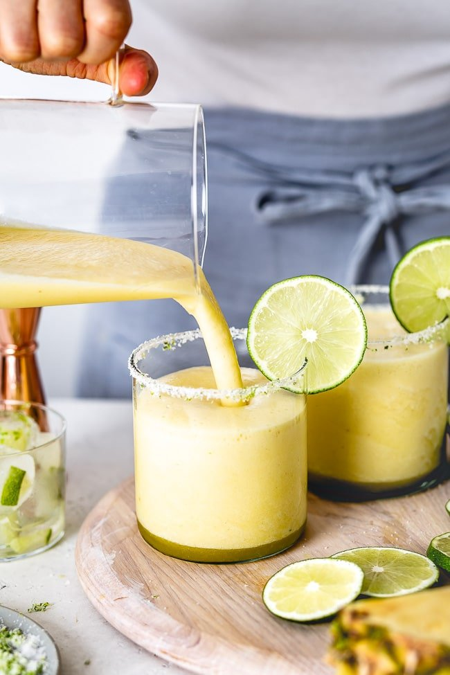 Frozen Pineapple Margaritas being poured in a glass