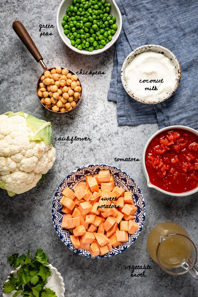 Cauliflower curry bowl Ingredients for the curry dish are placed in bowls and photographed from the top view