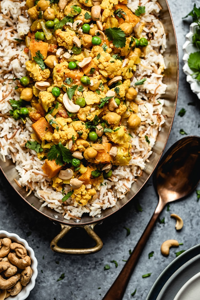 Cauliflower curry with coconut milk and sweet potatoes is placed in a copper pan and photographed from the top view