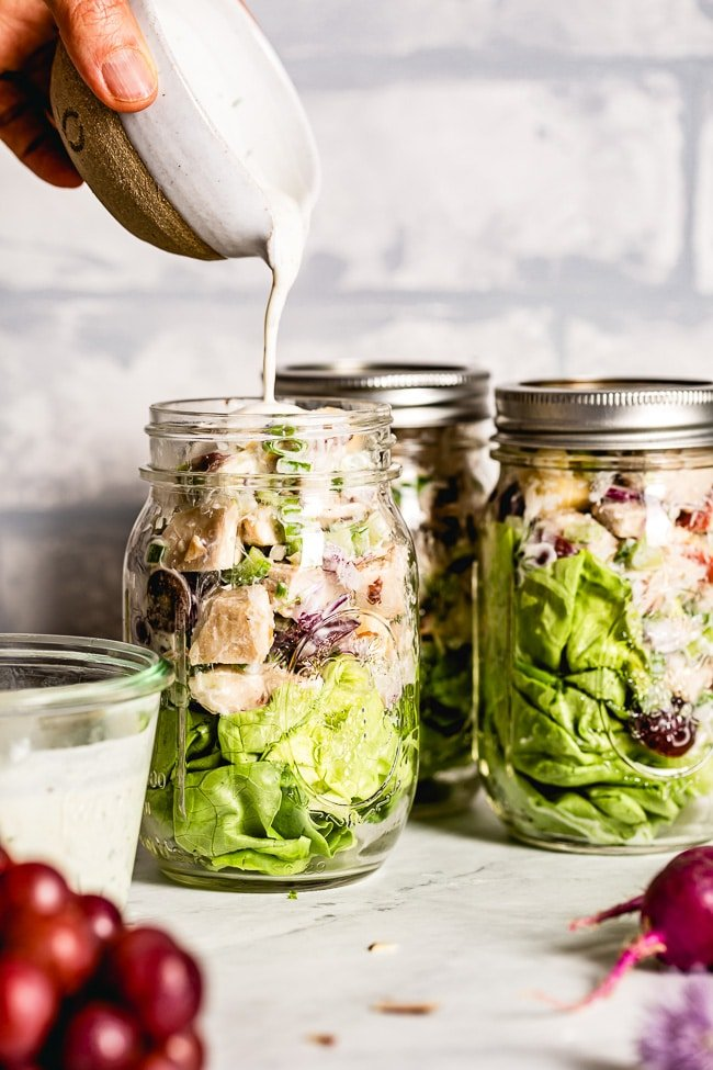Salad in A Jar is being drizzled with the Dressing