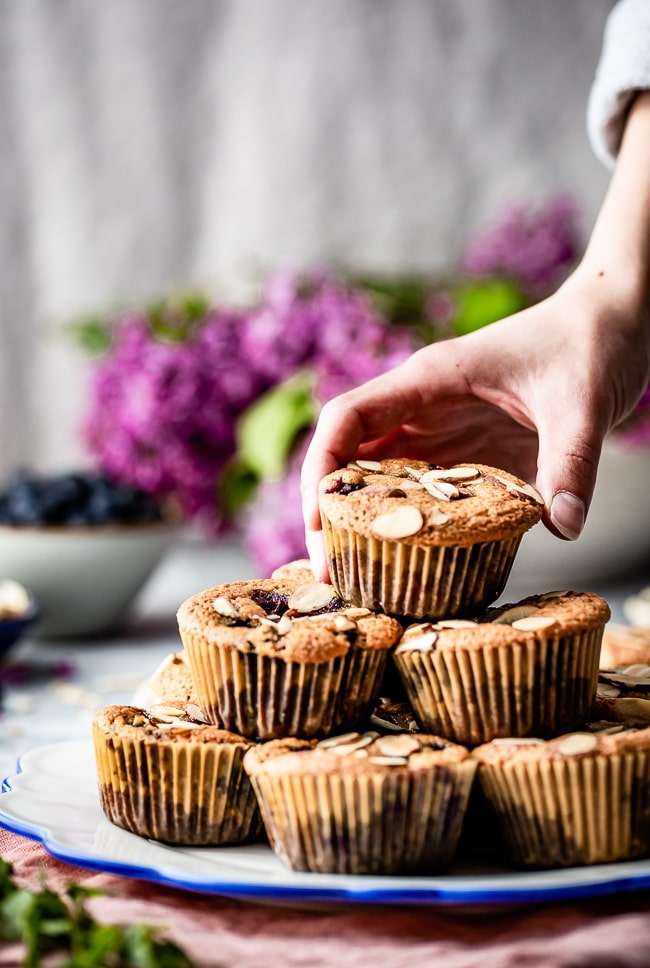 A woman is photographed as she is grabbing a berry muffin made with almond flour and maple syrup.
