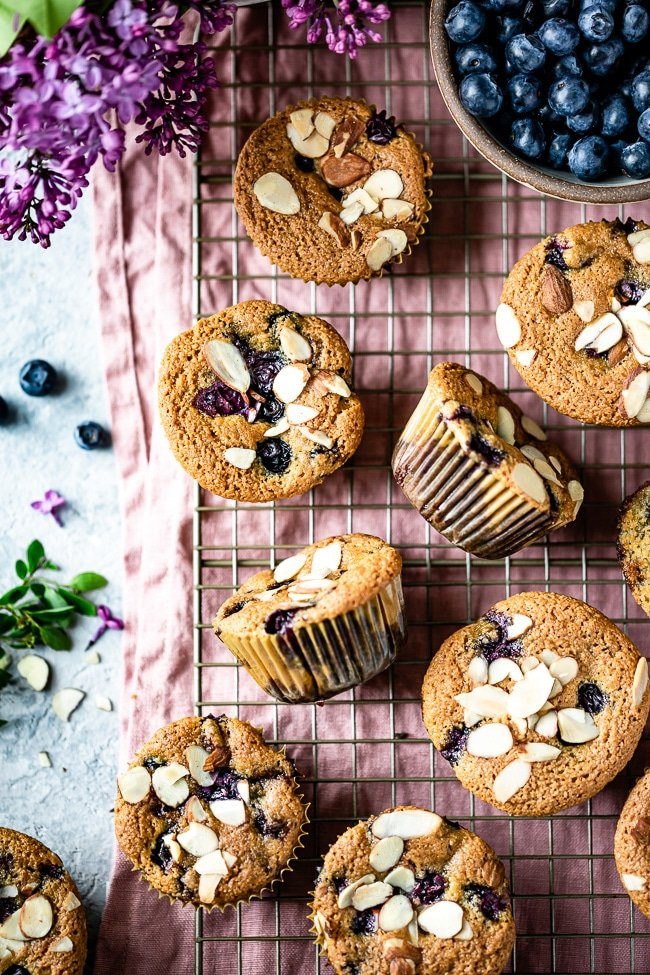 Gluten Free Blueberry muffins with almond flour are photographed from the top view with spring flowers.