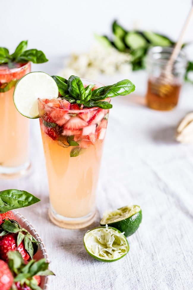 A glass filled with strawberry basil drink is garnished with strawberries, basil and lime photographed from the front view.