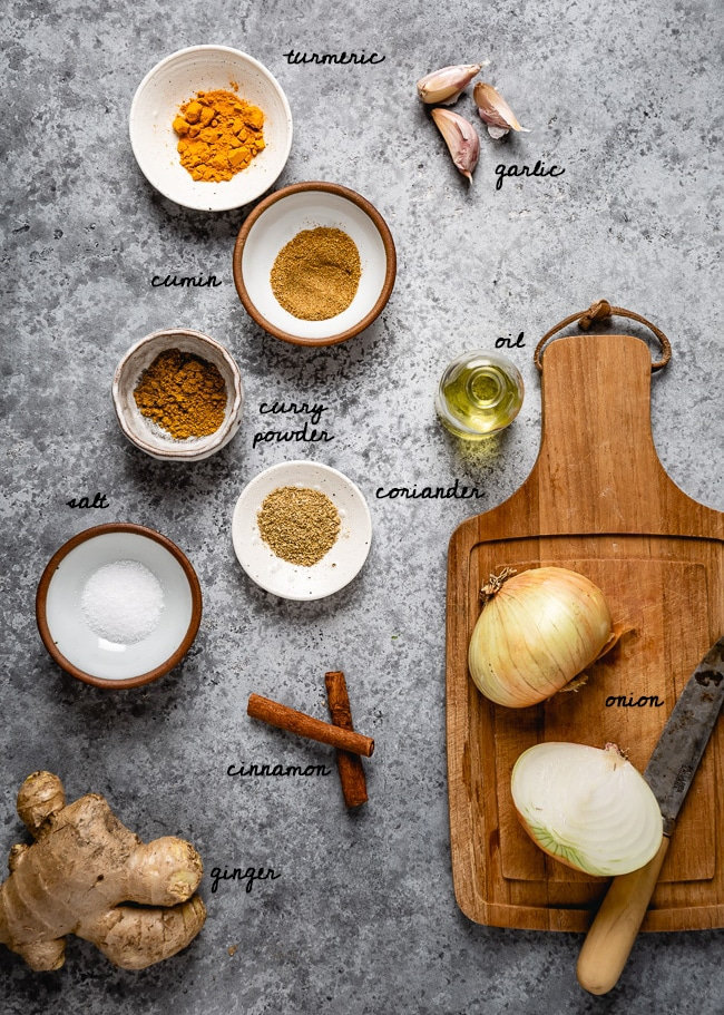 Spices, onion, and garlic for this recipe are laid out and photographed from the top view