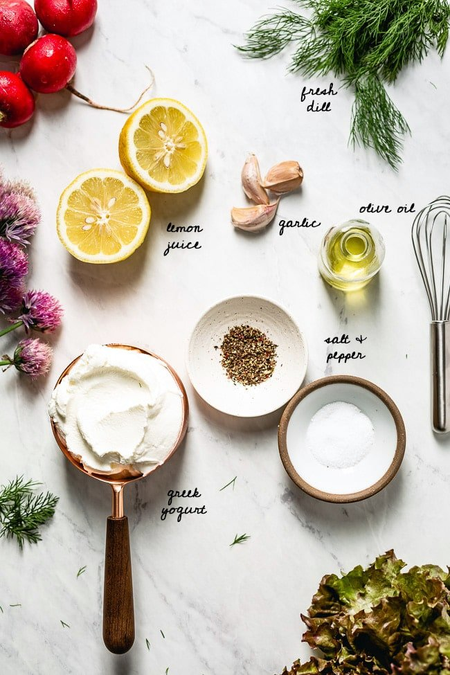 Ingredients for the dressing laid out on a marble background