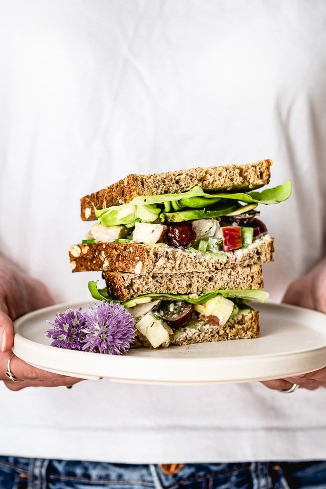 Greek Yogurt Chicken Salad Sandwich photographed in a woman's hands.