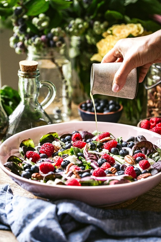 A woman is photographed as she is drizzling a blueberry feta salad with olive oil and lemon dressing.