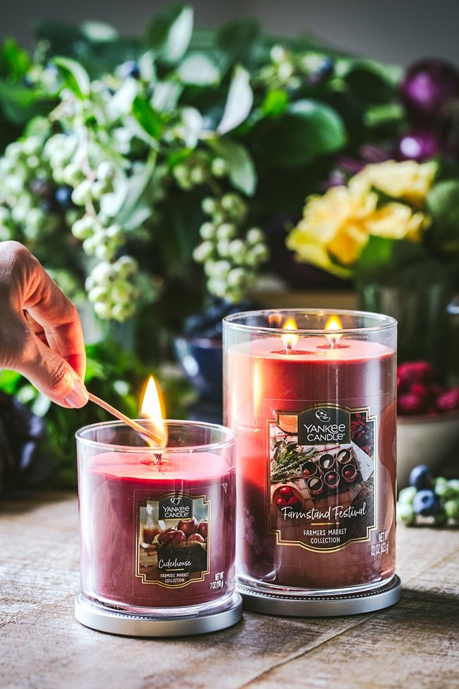 A woman is photographed as she is lighting up a Yankee candle with the blueberry salad in the background.