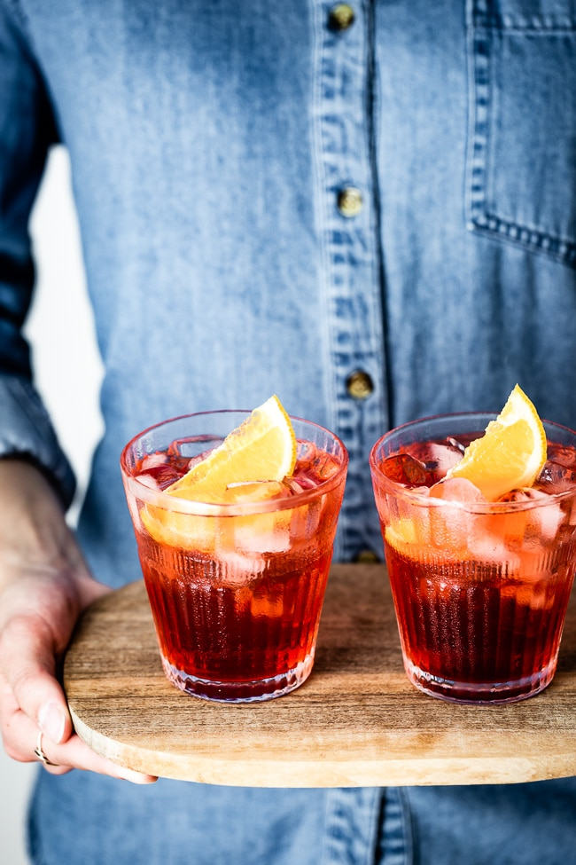Two glasses of negroni photographed  in a woman's hand