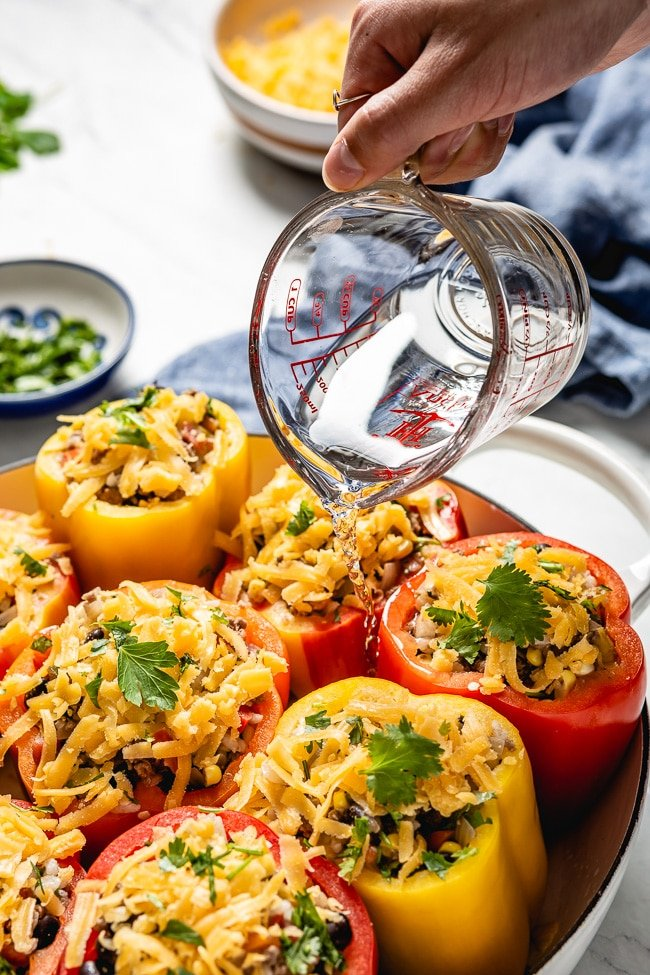 Mexican Style Stuffed Bell Peppers are filled with water to create steam in the oven.