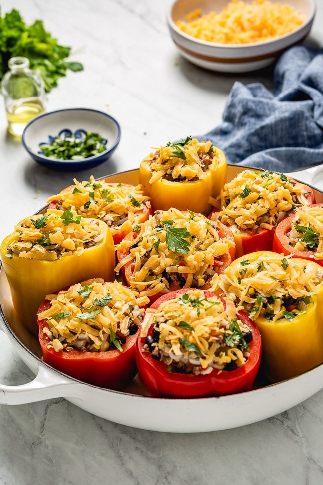 Rice and bean filled Peppers topped off with cheese photographed before they went into the oven