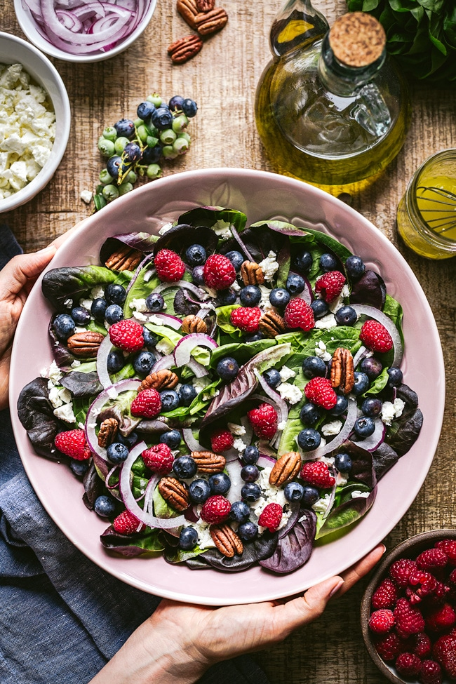 Blueberry salad mixed with pecans, spinach, feta, red onion and photographed as it is being served on a wooden board.