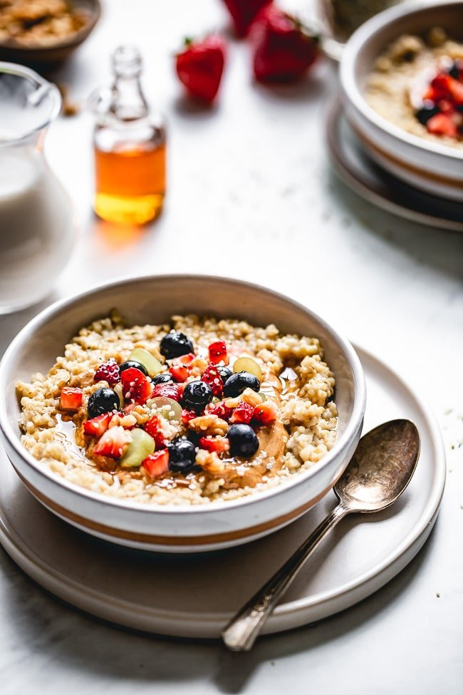 A bowl of Instant Pot Steel Cut oats topped off with fruits and photographed with a small jar of maple syrup photographed from the front view.