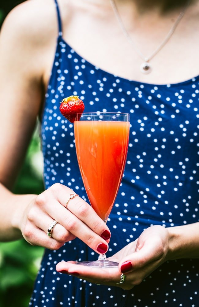Blood Orange Mimosa garnished with a strawberry photographed in a woman's hand.