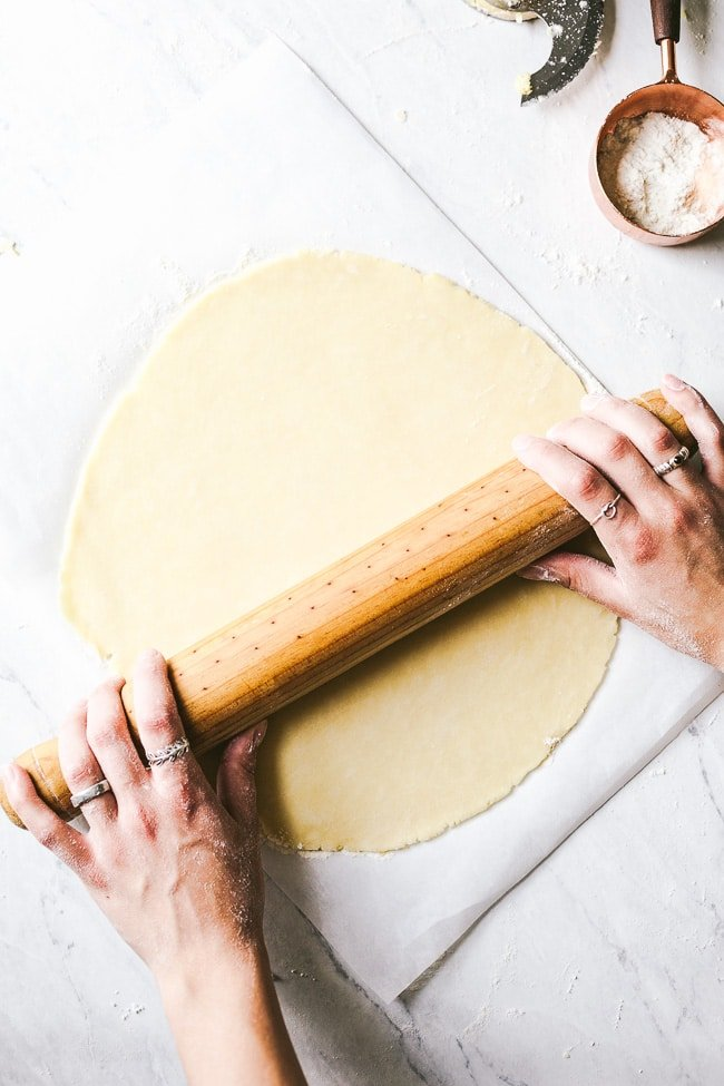 Learn how to make homemade galette dough from scratch - a woman is rolling galette dough