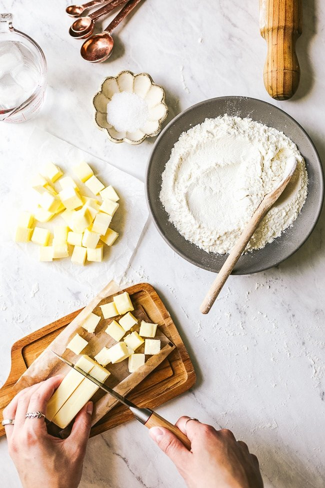 Ingredients for the easy galette dough recipe - Salt, flour, butter, and water are photographed from the top view.