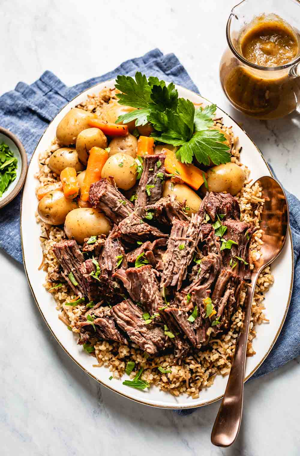 Shredded Instant Pot Chuck Roast (aka London Broil) placed on a plate along with potatoes and carrots photographed from the top view.
