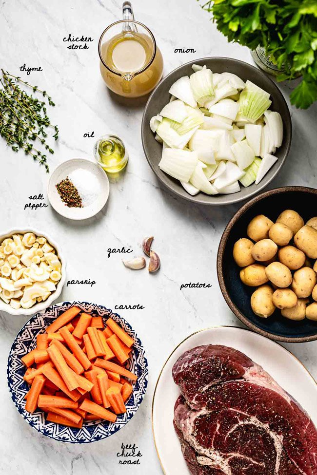 Ingredients: Onion, chicken stock, oil, carrots, potatoes, parsnips, and beef chuck, are photographed from the top view.