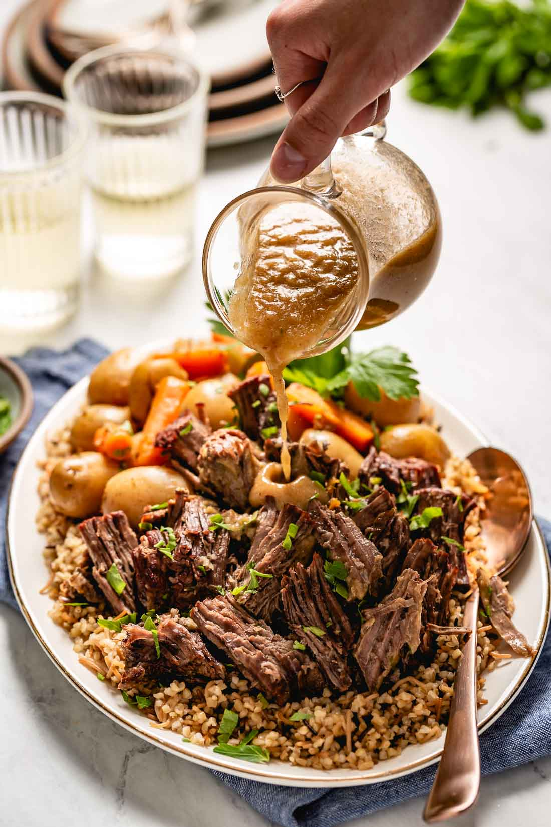 Easy Instant Pot Pot roast and potatoes recipe is photographed from the front view as a woman drizzles it with gravy.