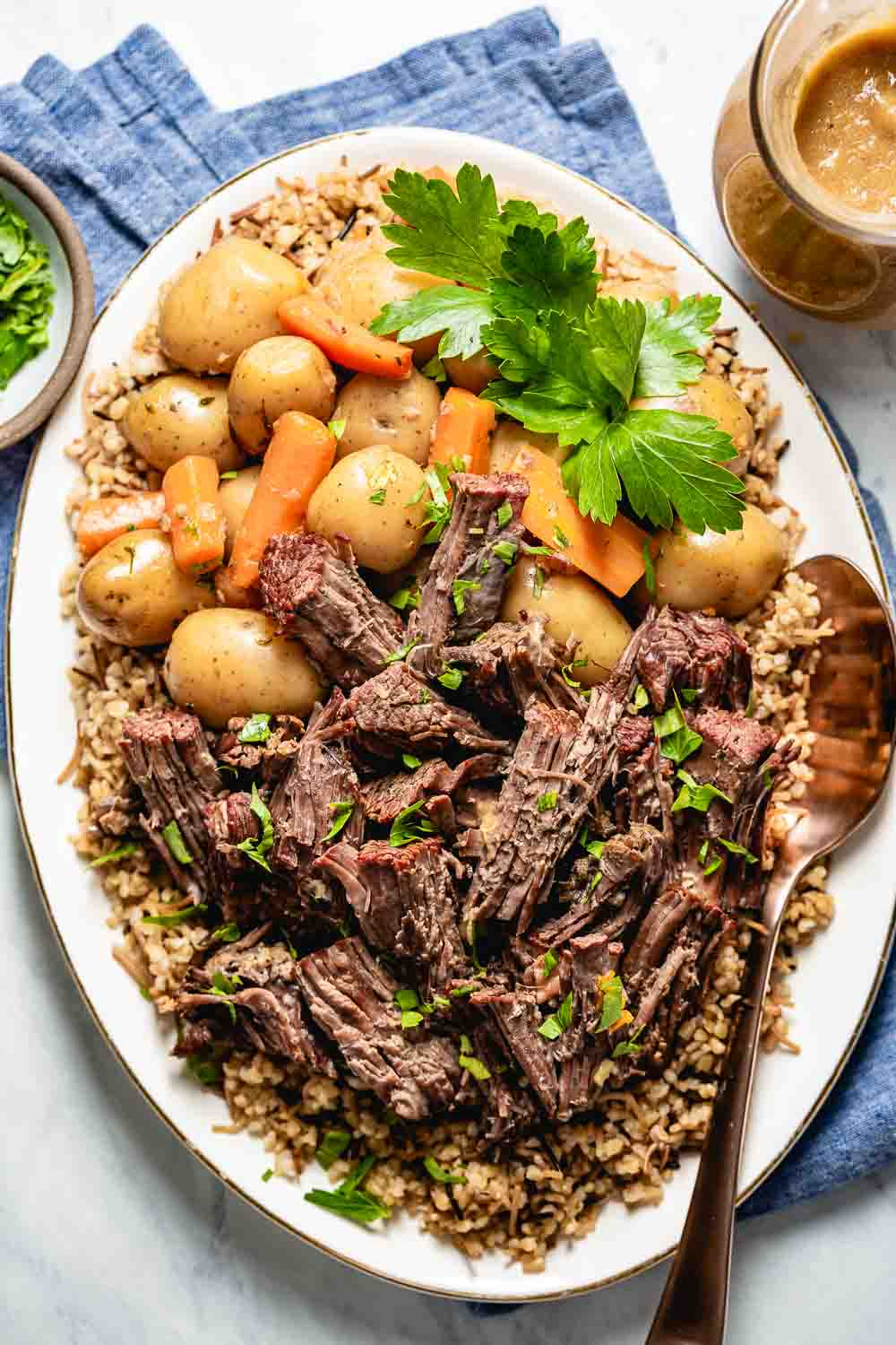 Pressure Cooker Pot Roast recipe served with potatoes and carrots over a bed of bulgur pilaf and garnished with fresh parsley photographed from the top view.