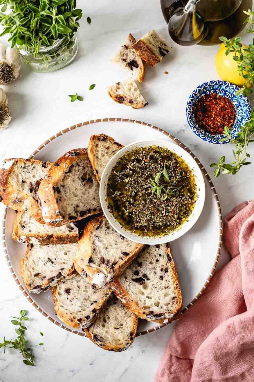 Olive bread served with olive oil dipping dish photographed from the top