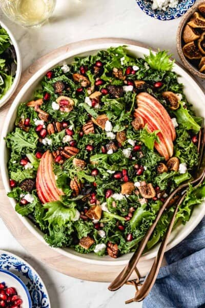 Fall harvest salad in a bowl with spoons on the side