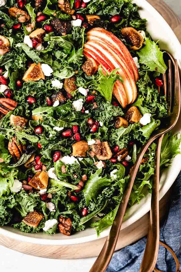 Harvest Kale Salad packed with apples, figs, and goat cheese photographed from the top view.
