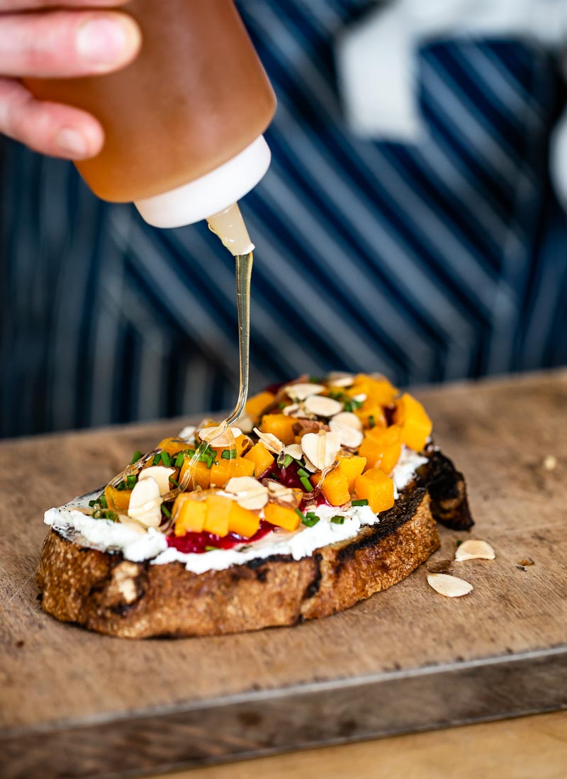 Goat cheese bruschetta with roasted butternut squash is being drizzled with honey