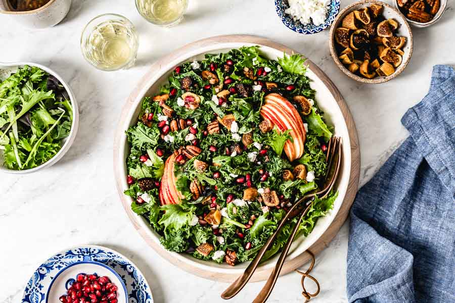 Winter Harvest Salad recipe photographed from the top view with figs, goat cheese, and pecans around it.
