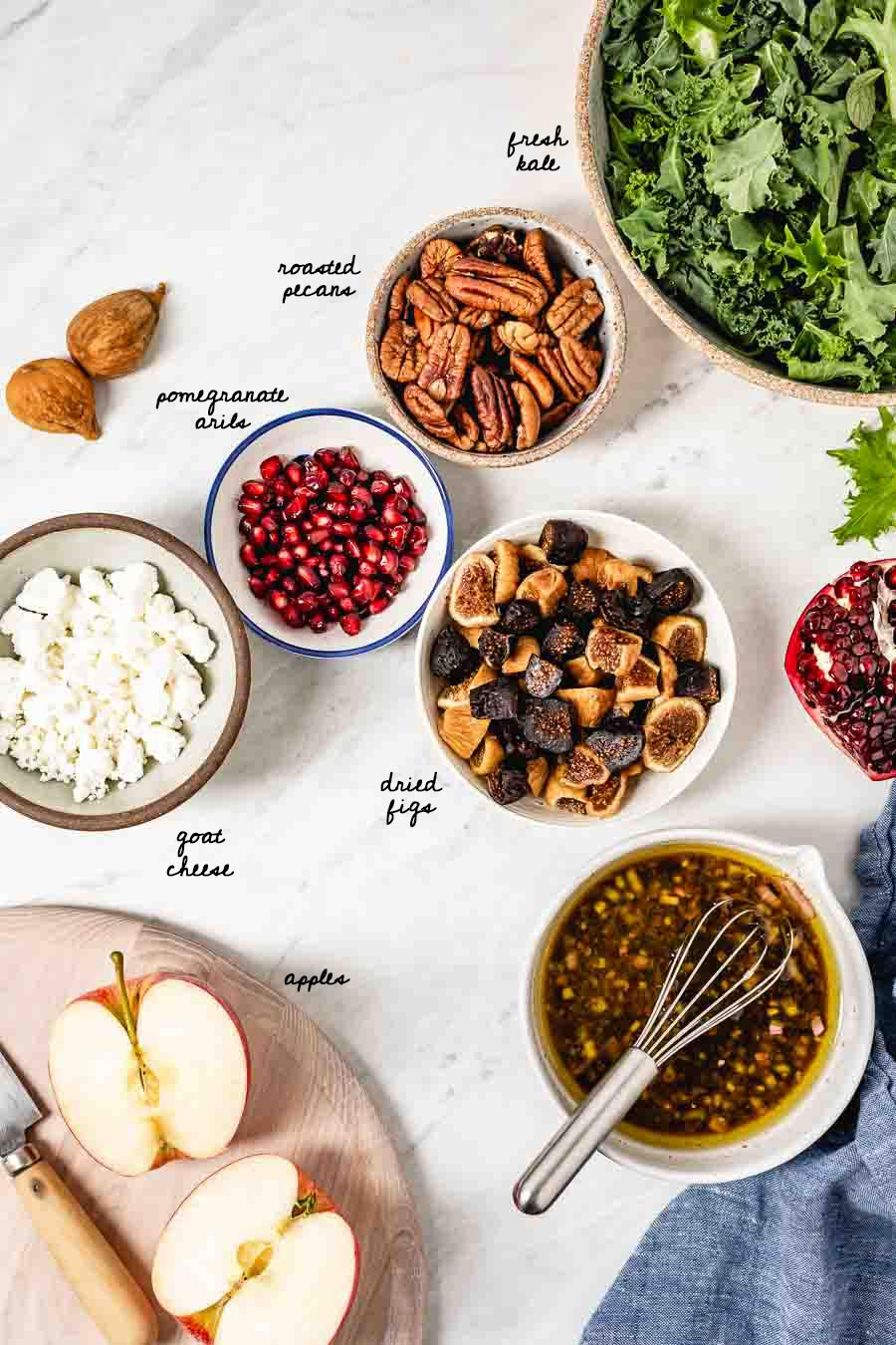 Harvest Kale Salad Ingredients: Kale, pecans. pomegranate arils, goat cheese, figs, and apples are photographed from the top view.