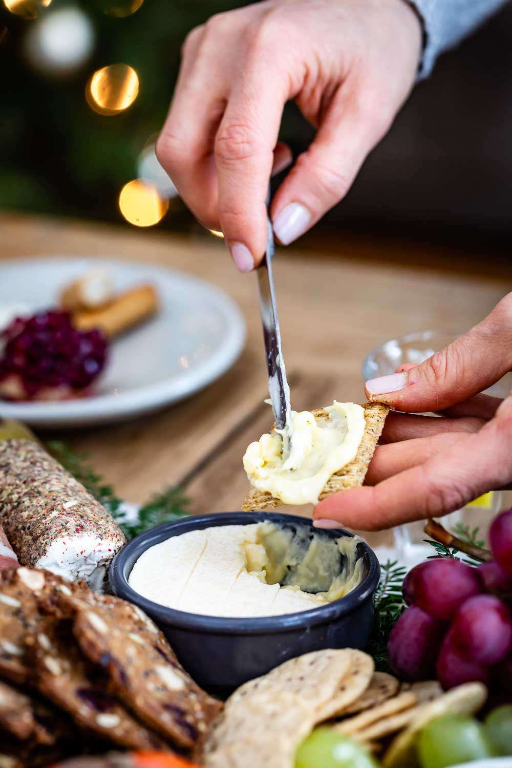 A woman is spreading goat cheese dip on a cracker