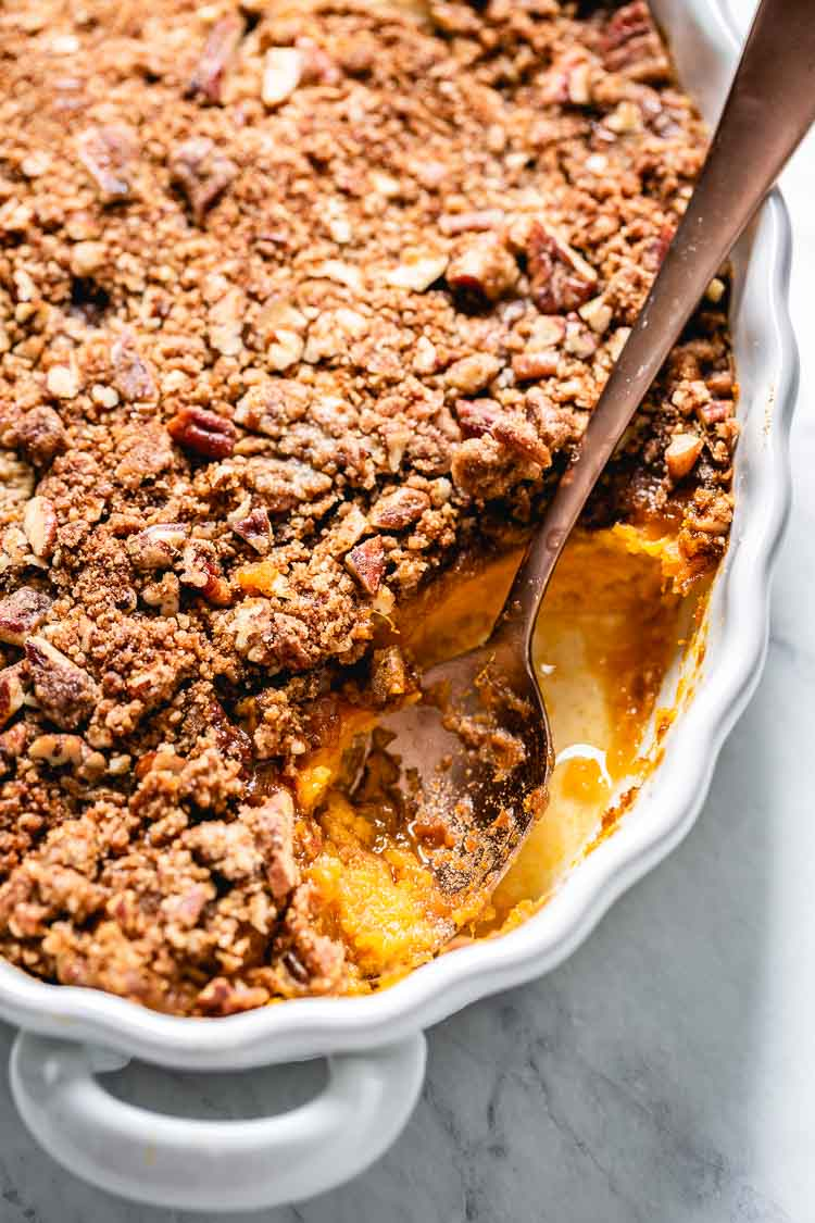Sweet potato souffle with a spoon on the side in a casserole dish