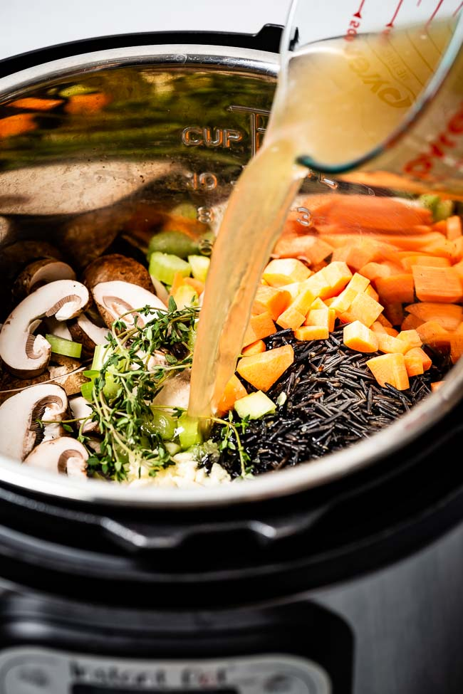 All ingredients are placed in an instant pot and photographed from the front view as chicken stock is being poured into it.