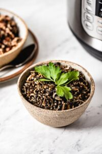 Instant Pot Wild Rice Recipe cooked and placed in a bowl. Photographed in front of a pressure cooker