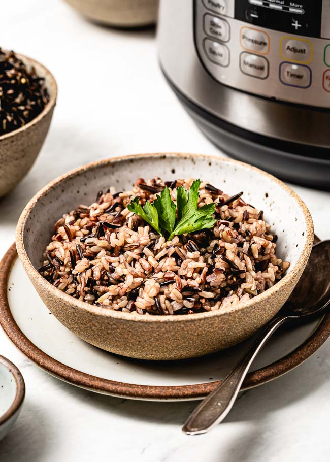 A bowl of my Instant Pot Wild Rice Blend recipe is photographed in front of a pressure cooker.
