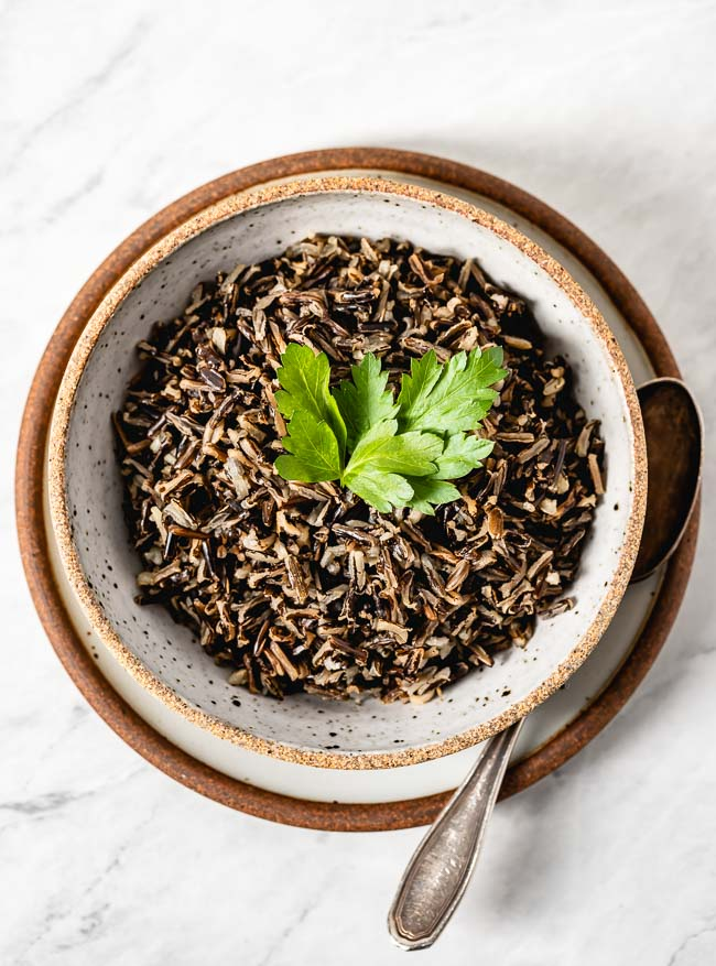 A bowl of wild rice blend with a spoon on the side