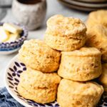 Sweet Potato Biscuits Recipe - Biscuits are placed on a plate on top of each other with butter in the background