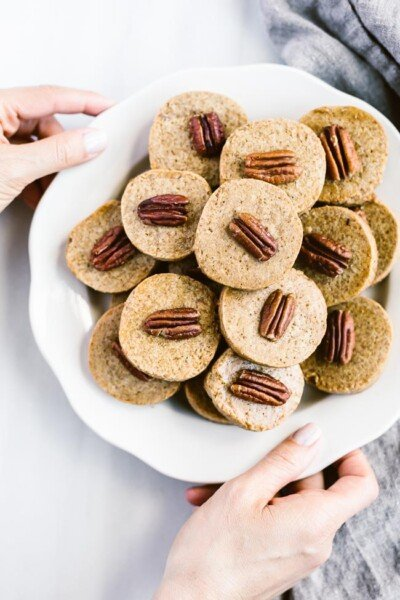 Pecan Shortbread Cookies are served by a woman photographed from the top view.